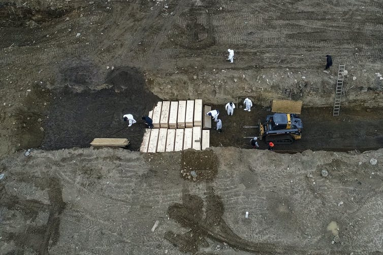 Workers wearing protective equipment place coffins in a trench.