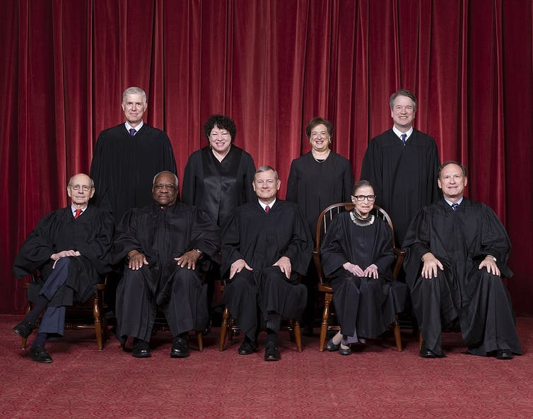 Official portrait of the nine justices wearing their black robes, against a red background