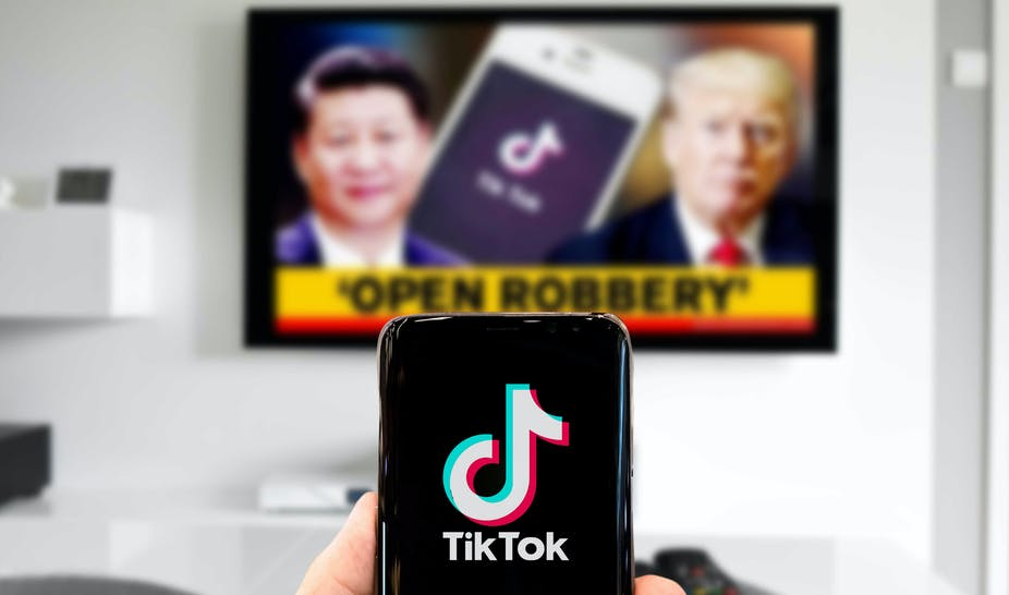 A person looks at TikTok on their phone while Donald Trump and Xi Jinping appear on a TV in the background.