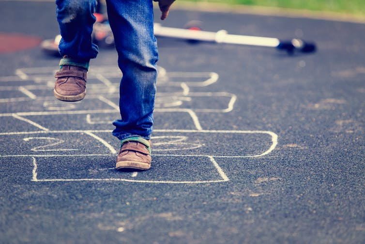 Legs and feet of child paying hopscotch.