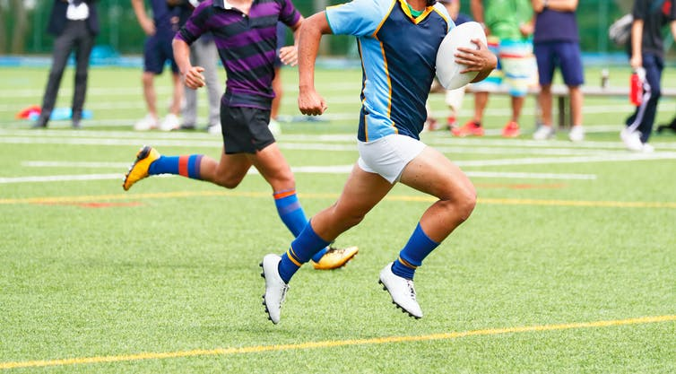 Two players in a game of school rugby, one running with the ball.