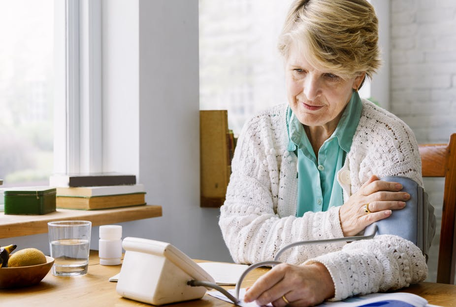 A woman taking her blood pressure using an electronic device