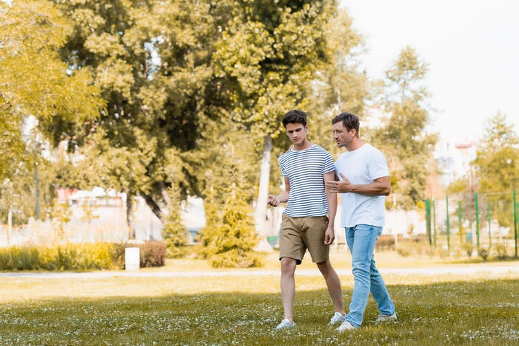 Father and teenage son walking and talking outside in a park.