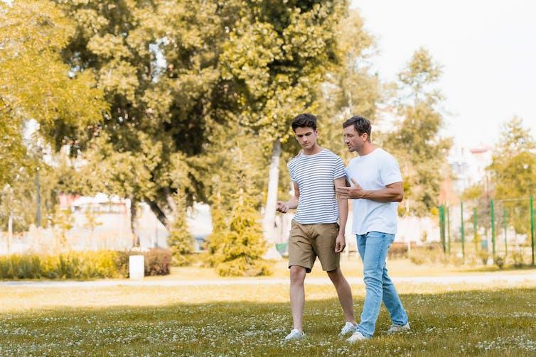 Un padre y su hijo adolescente hablan mientras pasean por un parque.
