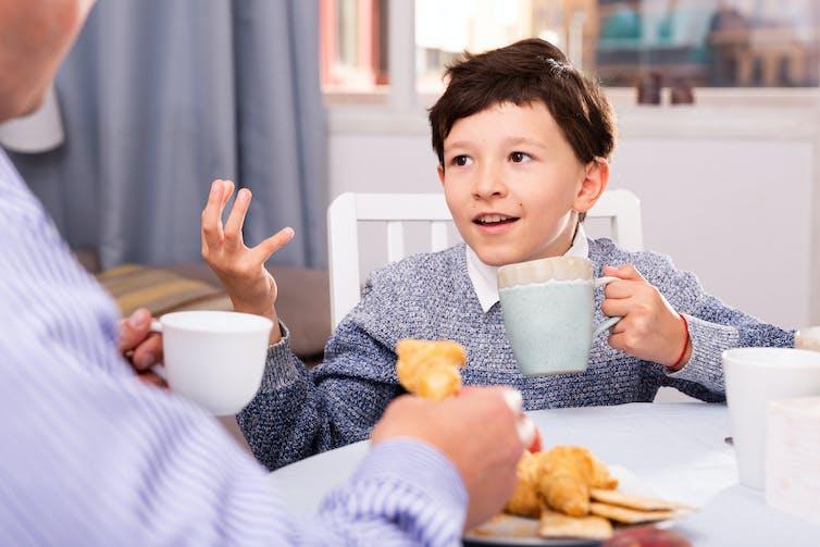Un niño habla con un adulto mientras bebe de una taza.