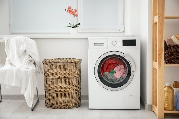 Washing machine next to laundry basket.