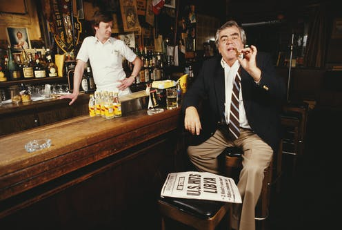 Jimmy Breslin smoking a cigar at a bar.