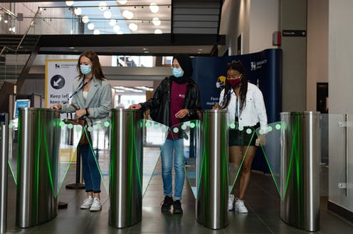 Three women wearing masks swipe their passes at a security gate