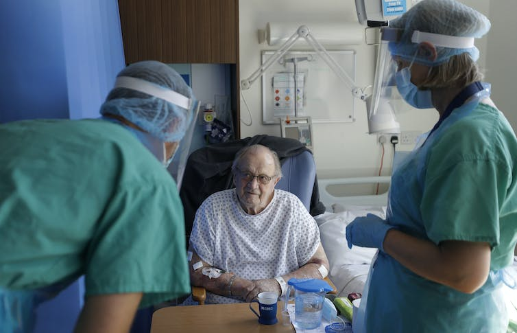 A patient in hospital, being attended to by two staff wearing PPE
