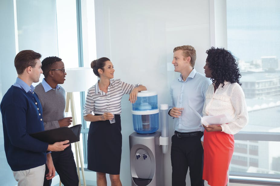 Five people in office clothes stood around a water cooler.