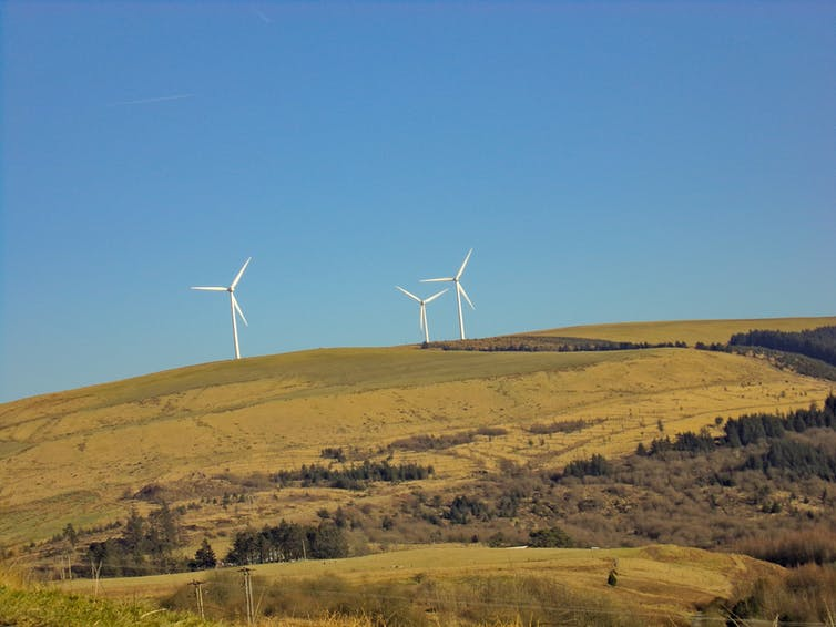 Wind turbines on a green hillside.