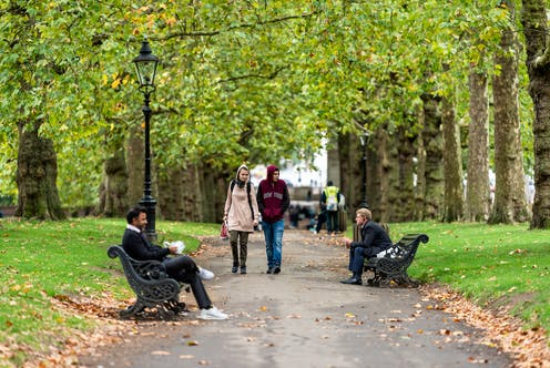 People walking and sitting on benches under trees