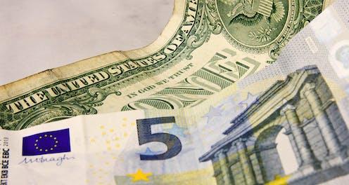 Billetes de cinco euros y de un dólar.