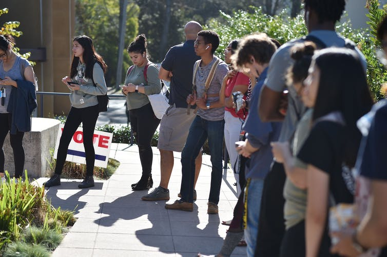 Students wait to vote at a polling station on the campus of the University of California, Irvine