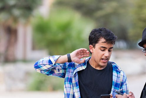 A white student and an African American student engage in an argument outside while holding their phones.