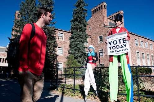 Man and woman on stilts in patriotic outfits hold a sign reading 'Vote Today on Campus' and talk to a student