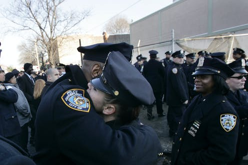 A male and a female police officer hug.