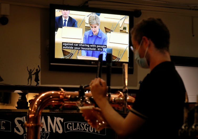 A man pulls pints in a pub while a television show Nicola Sturgeon addressing the Scottish parliament