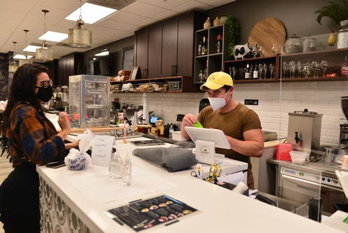 A man and a woman in masks work in an empty restaurant at the counter.