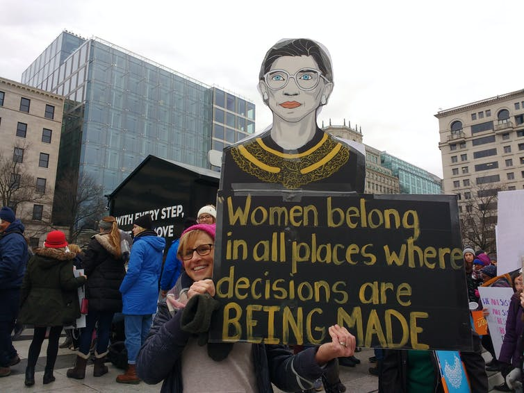 Woman in red hat at protest holding up a sign with an image of Ruth Bader Ginsburg and the text 'Women belong in all places where decisions are being made'