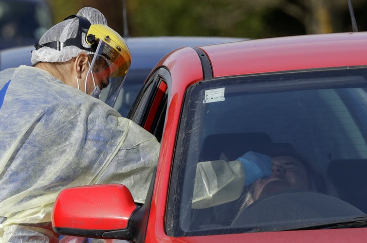A medical person reaching into a car window to carry out a COVID-19 test on the driver.