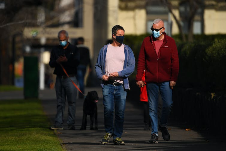 People walking through a Melbourne street wearing masks.