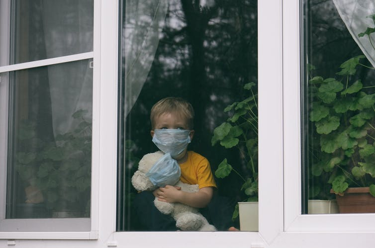 A child and a teddy, both wearing masks, look out a window.