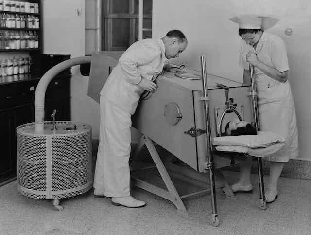 Polio patient in an iron lung to help them breathe.