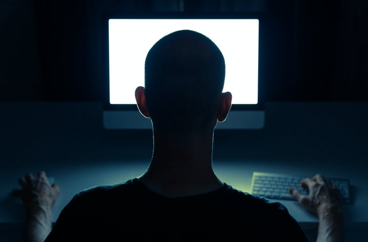 Picture of a man from behind staring at a computer screen.
