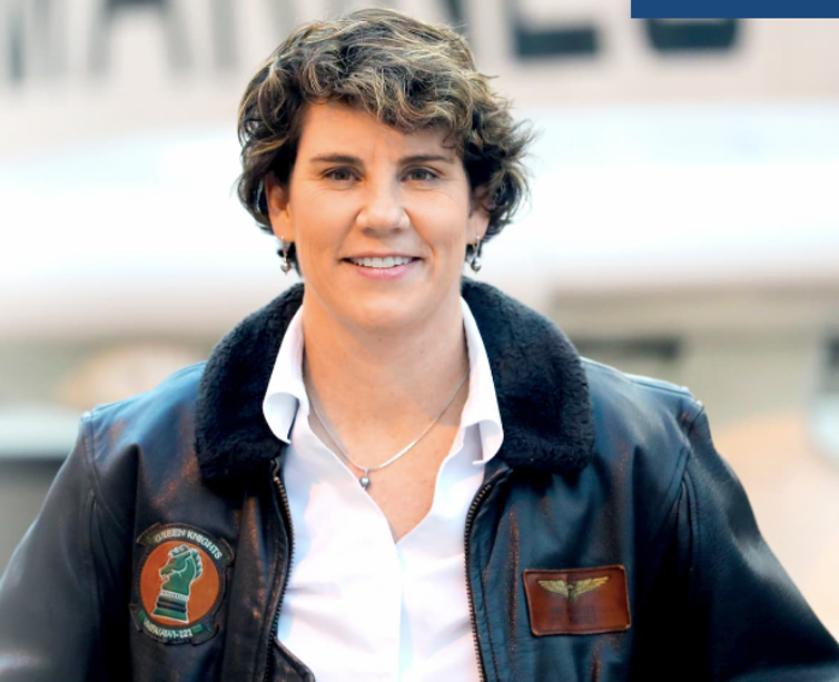 Amy McGrath in a flight jacket and open-collared shirt.