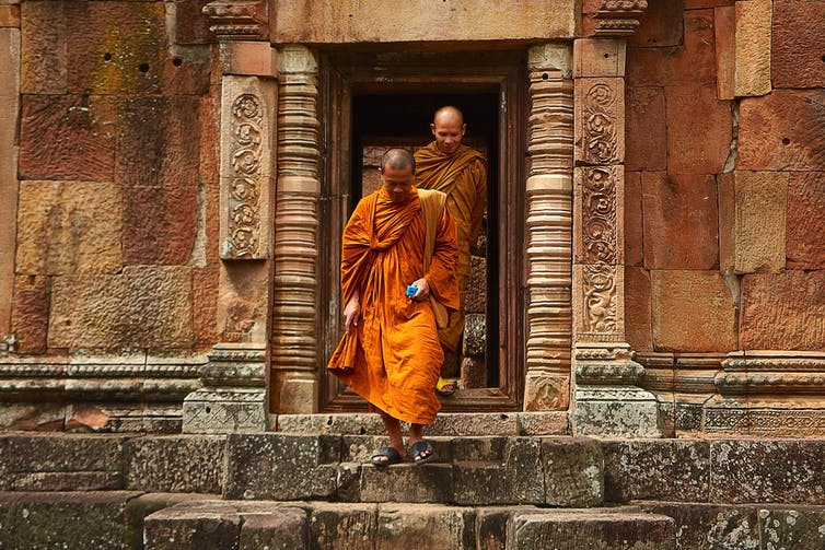 Two monks in orange robes walking down concrete stairs.
