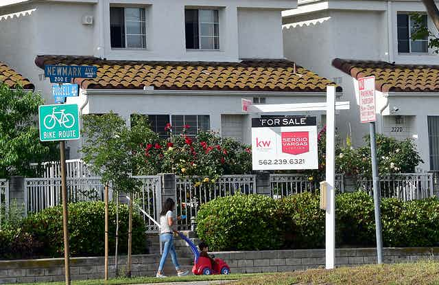 A for sale sign in front of a white California home, with a woman walking with her child on the sidewalk
