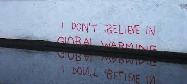 Pintada en una pared blanca que dice No creo en el cambio climático, con varias palabras tapadas por el agua.