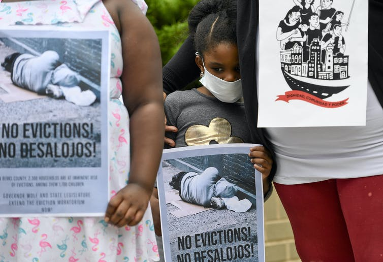 A young girl holds a bilingual sign reading 'no evictions/no desalojos' while being comforted by her sister