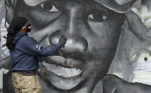 A man in a facemask holding a spraypaint can completes a mural paying tribute to Ahmaud Arbery.