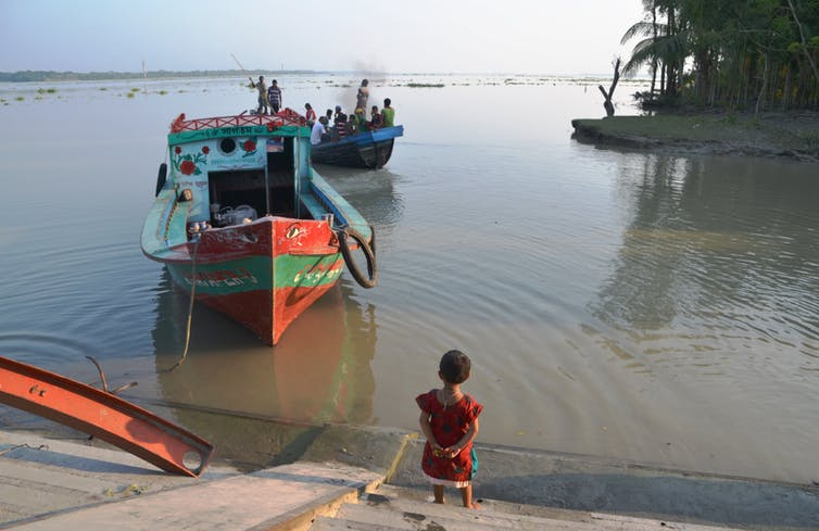 A young girl stands on a concrete bank as a red, wooden boat returns from fishing.