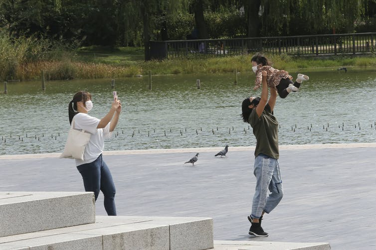 A person swings a baby up in the air as a woman takes a photo, all three wearing masks.