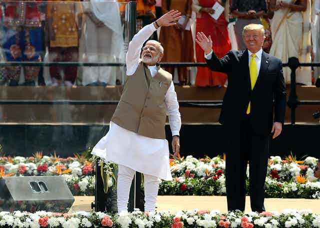 Indian Prime Minister Narendra Modi and U.S. President Donald Trump wave to a crowd.