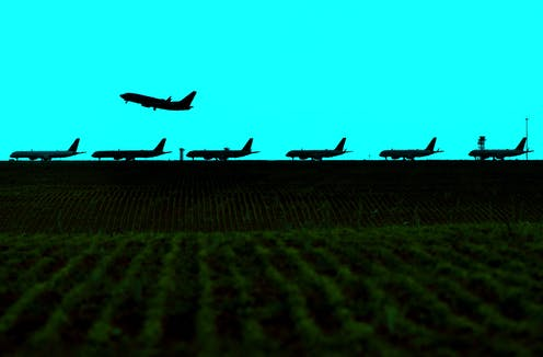 Photo illustration of an airplane taking off over a line of parked aircraft in April 2020.