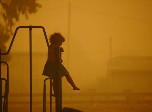 A child sits alone in a playground where the air is yellow due to bushfire smoke.
