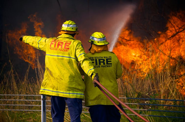 Two firefighters face a blaze.