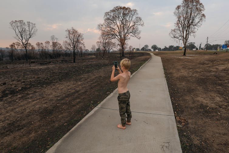 A young child photographs a burnt out landscape