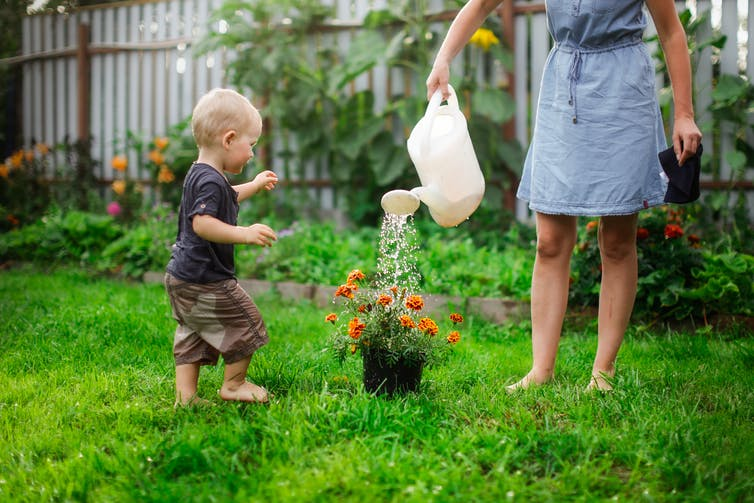A parent and child water a garden.