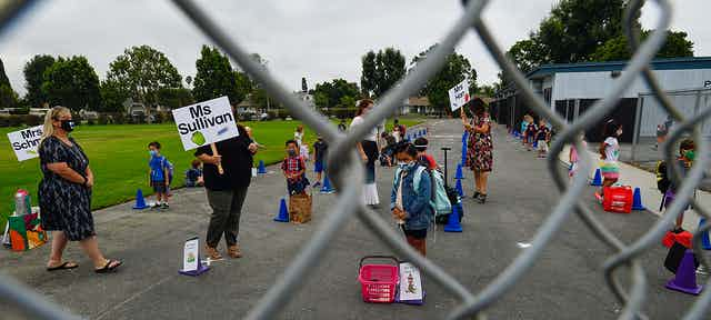 Teachers hold signs with their names as children gather outside their school wearing masks.