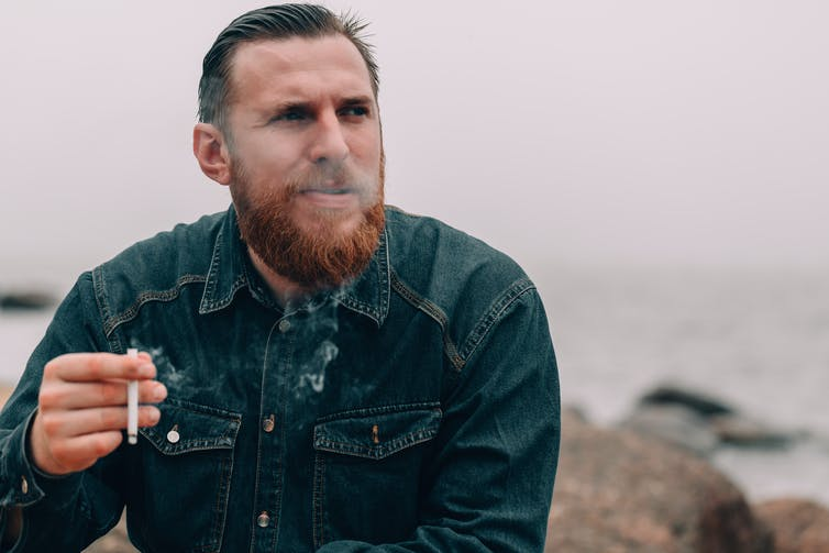 A man smokes a cigarette outdoors.