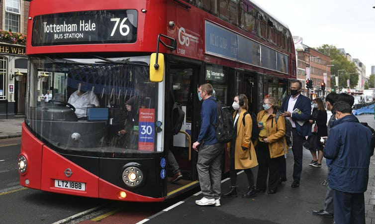 Londoners in mask line up for a bus