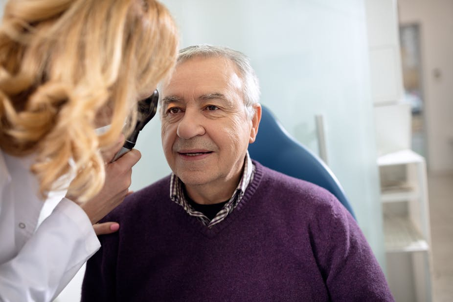 Older man has his vision tested by a female doctor.