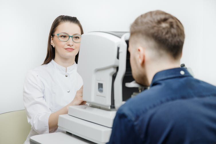 Man has his eyes tested using an OCT machine.