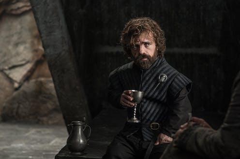 Tyrion Lannister de la série Game of Thrones, un verre à la main.