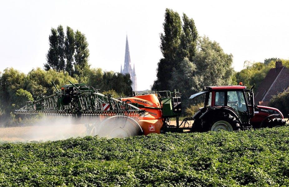 Un tracteur pulvérisant des pesticides sur des cultures.